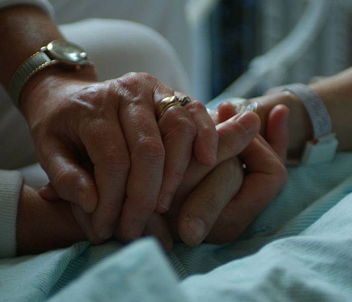 patient and caregiver holding hands