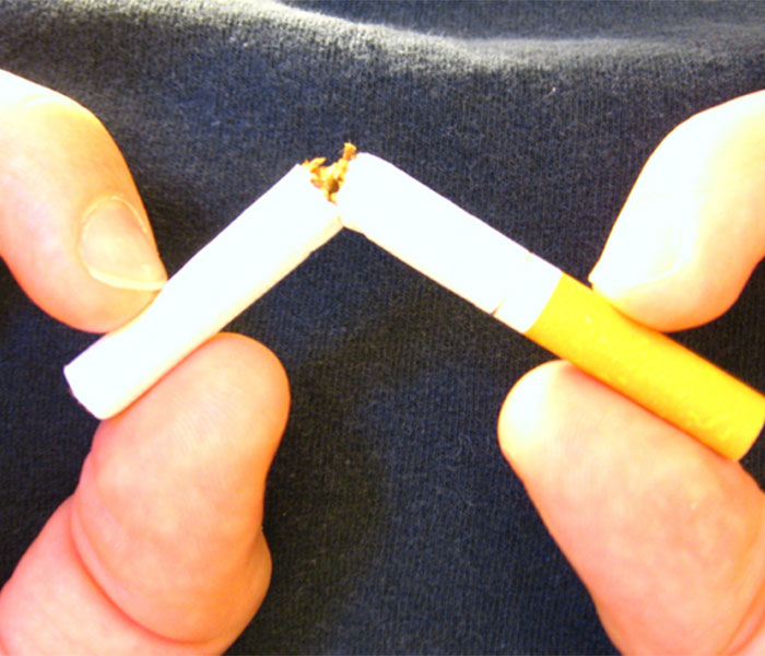 Smoker breaks cigarette in half