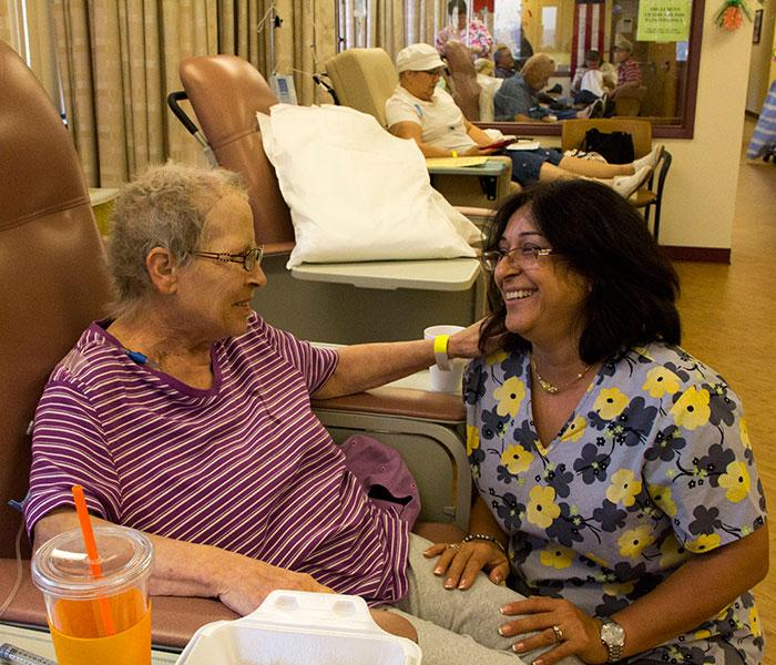 Oncology patient and nurse share a smile