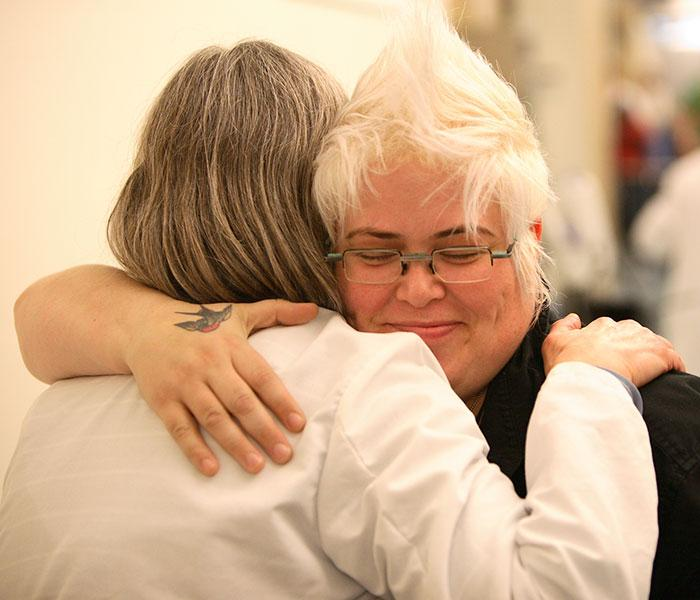 An onoclogy patient and her caregiver share a hug