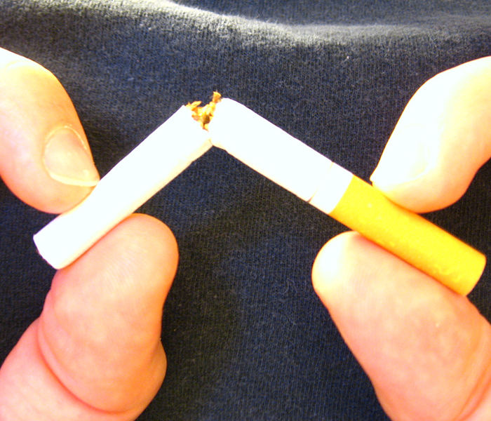 smoker breaking a cigarette in half